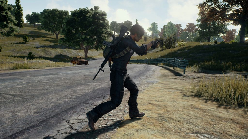 Playerunknown's Battlegrounds player firing a gun in the open.