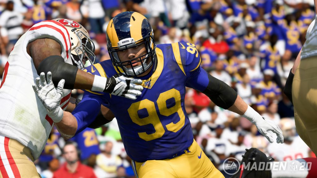 The defensive player from the LA Rams is getting past the offensive linemen from the San Fransico 49'ers.