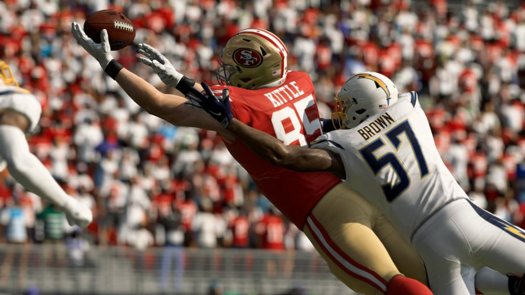 The wide receiver from the San Francisco 49'ers is diving to catch a pass with the defensive player on him.
