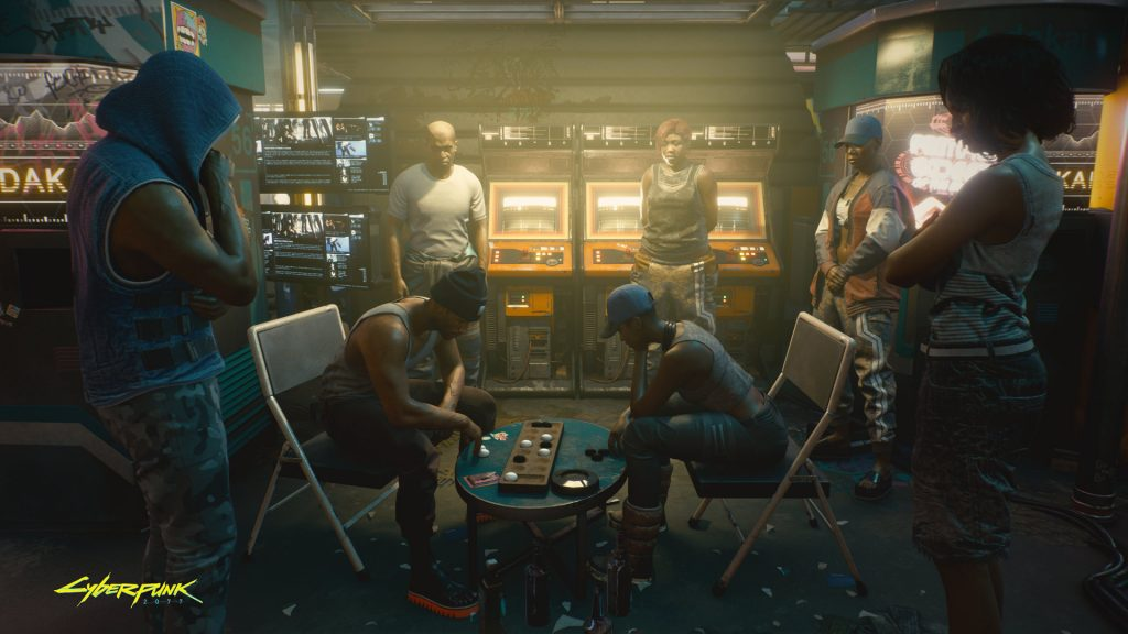 Group of 7 individuals gather round a small table in a gaming lounge to watch two of their number play an intense game.