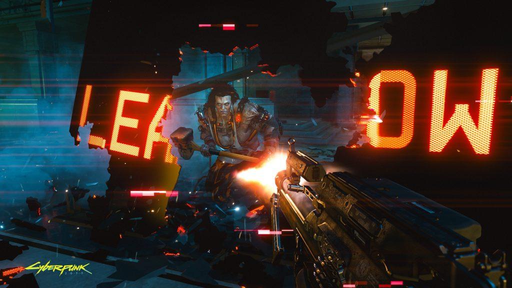 A terrifying cybernetic individual with a sledgehammer menacingly moves through wreckage of a digital sign as the player shoots at them.