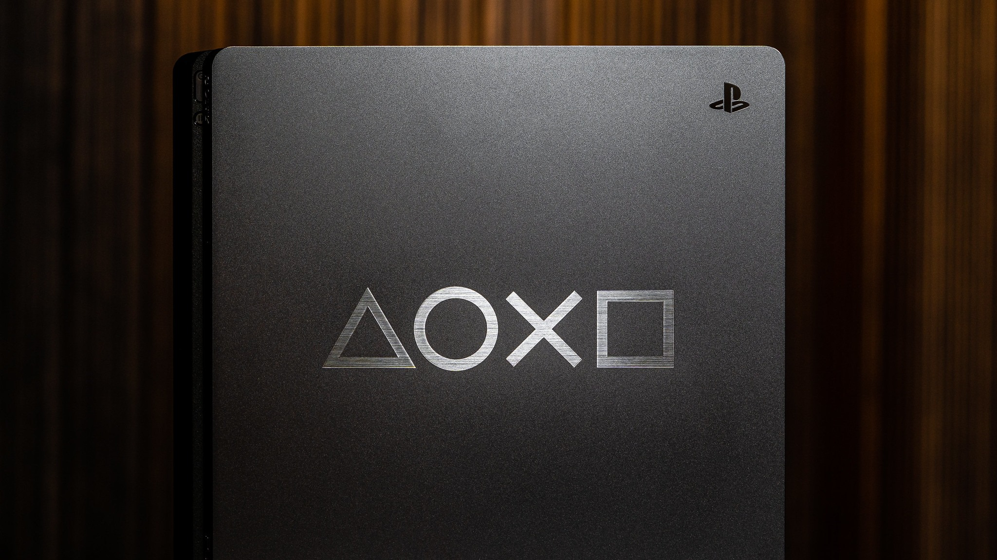 A picture of a very nice PS4 console. Nice moody lighting.