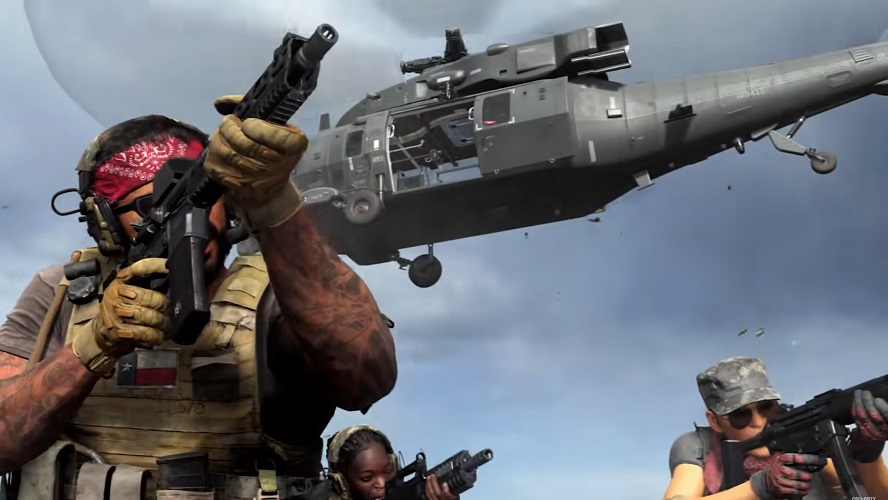 A military force with guns at the ready moves forward while a helicopter hovers above them