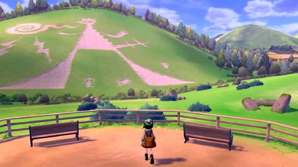 A pokemon trainer looks out over a vast hillside covered with strange symbols and dotted with trees