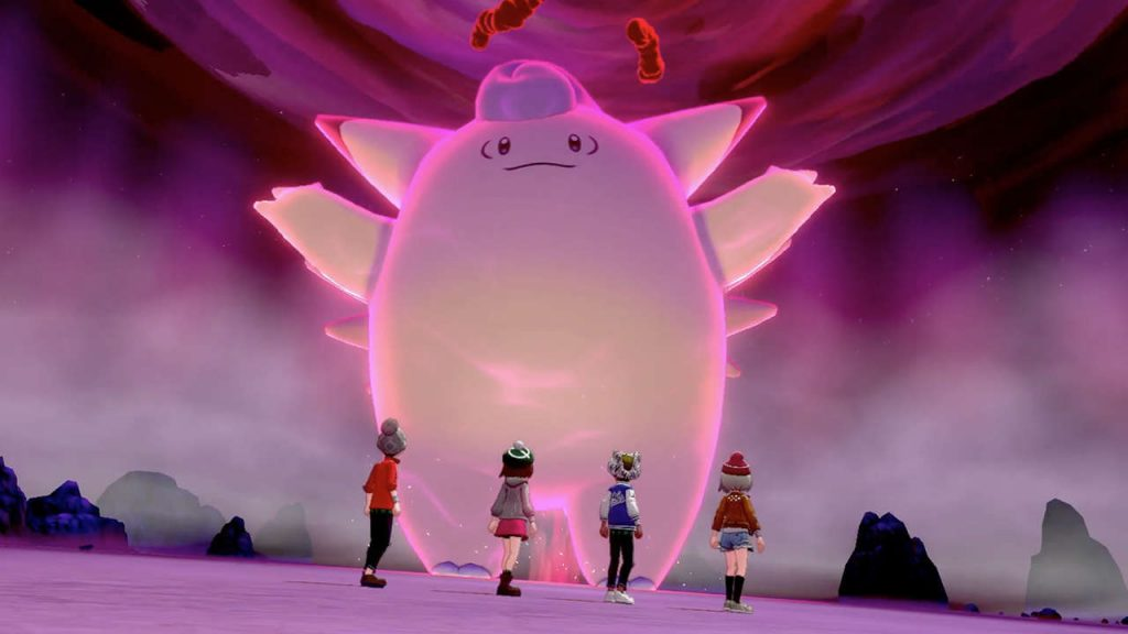 A gigantamax pokemon appears before trainers in a raid battle