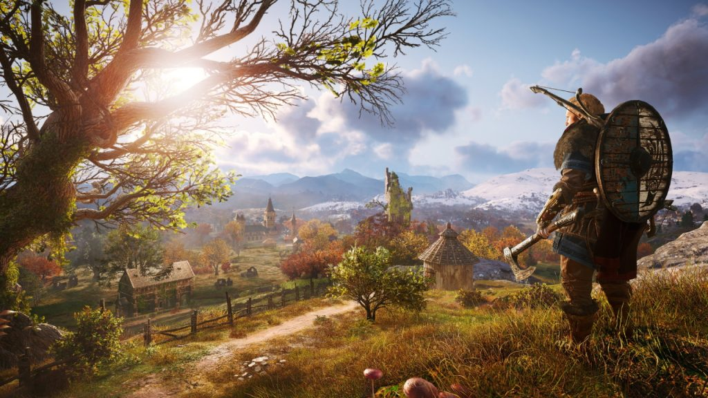 A viking man with shield, bow and axe stands on a hill overlooking a peaceful village setting in midafternoon. A tree to his left blocks some sunlight, but the rest settles over a small farm and settlement showing signs of fall foliage in the trees and faint clouds in the blue sky.