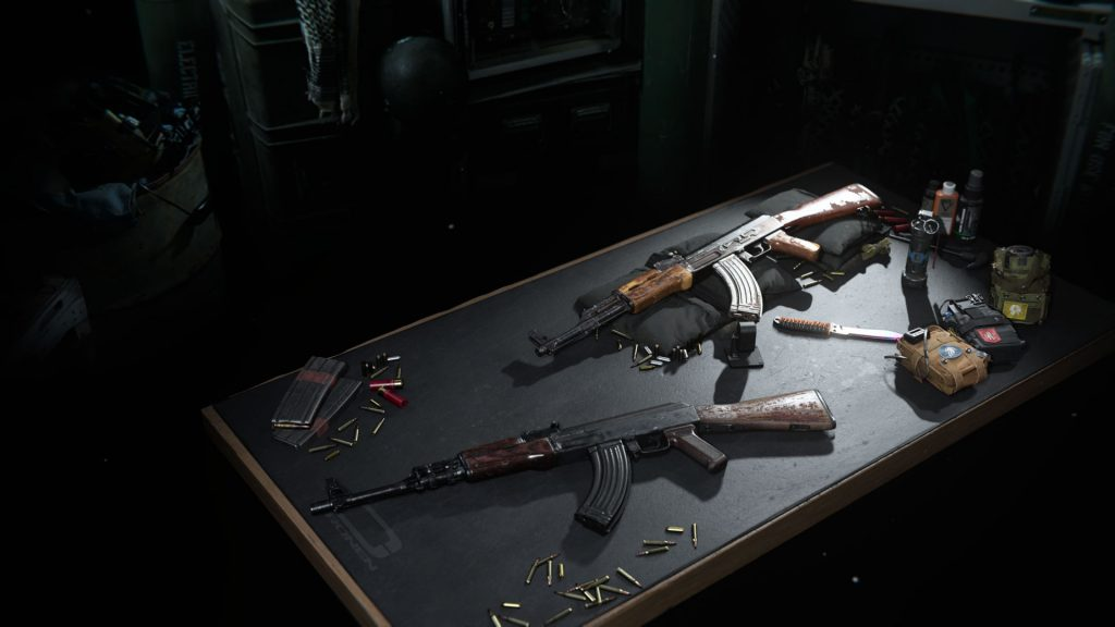 Two assault rifles lie on the gunsmith table.