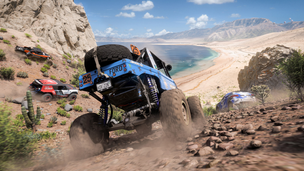 Off-road vehicles speed down a hill towards the Mexican coastline.